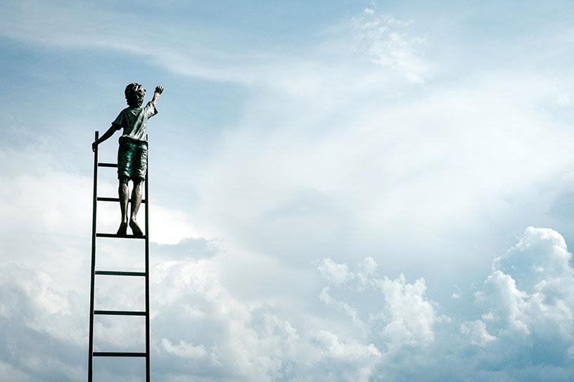 Kind auf Leiter greift Richtung Himmel