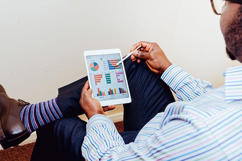 Mann schaut auf iPad mit Diagrammen