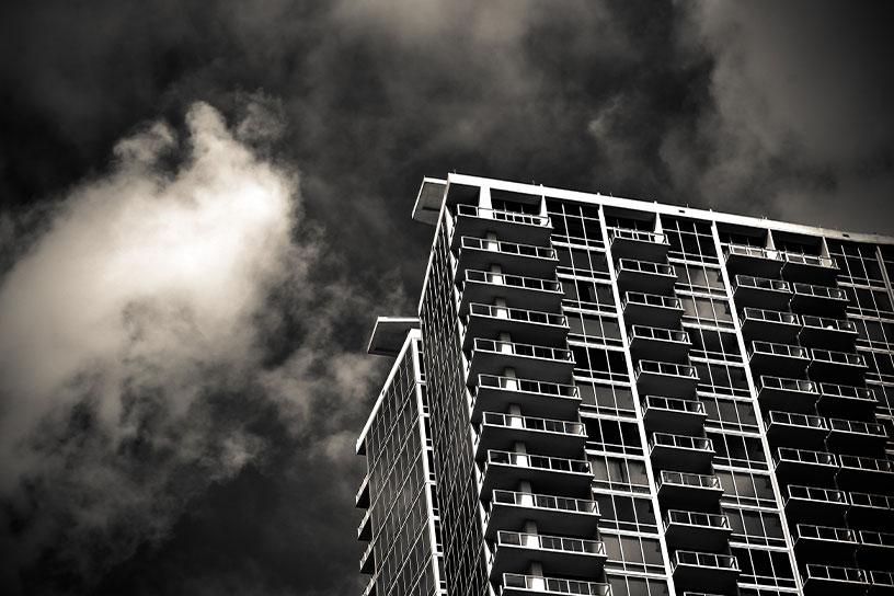 Schwarz Weiß Bild von einem Hochhaus  vor einem Wolkenhimmel