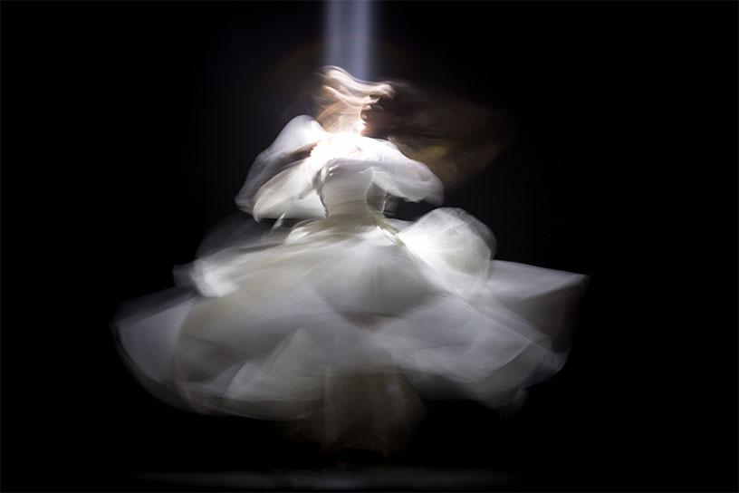 Schleierhaft Figur, die eine Seele darstellen soll. Weißes Kleid, mit einem Lichtstrahl von oben auf schwarzem Hintergrund.