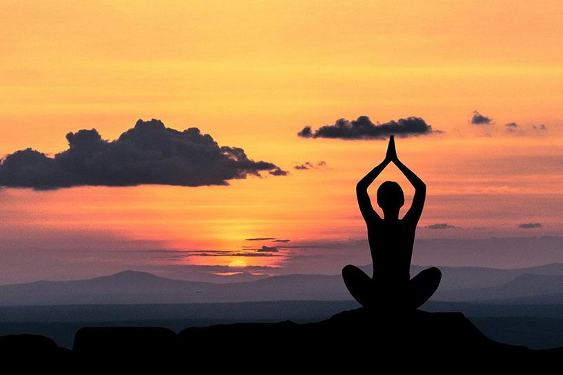 Silouette eines Menschen der Meditiert. Im Hintergrund sieht man einen orang/roten Sonnenuntergang zwischen fernen Bergen.