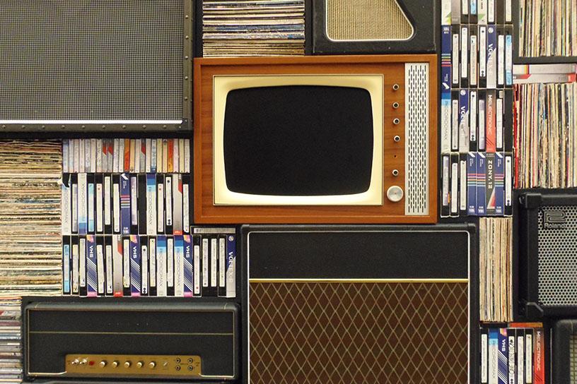 Alter Fehrnseher und Videokasetten in einem Regal, umgeben von alten Lautsprechern.