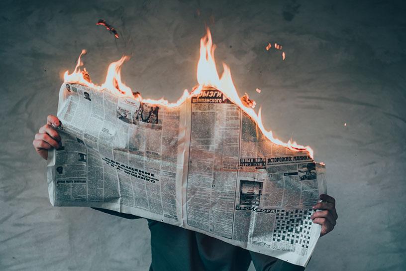 Mensch mit einer brennenden Zeitung in der Hand.