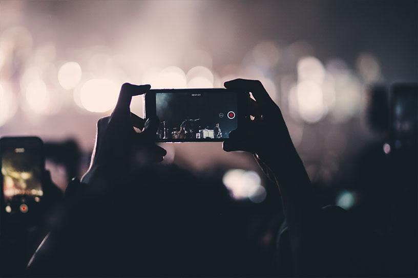 Mensch der ein Smartphone hochhält und ein Konzert filmt.