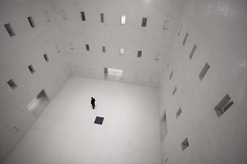 Mensch in einem weißen Raum mit vielen Fenstern.