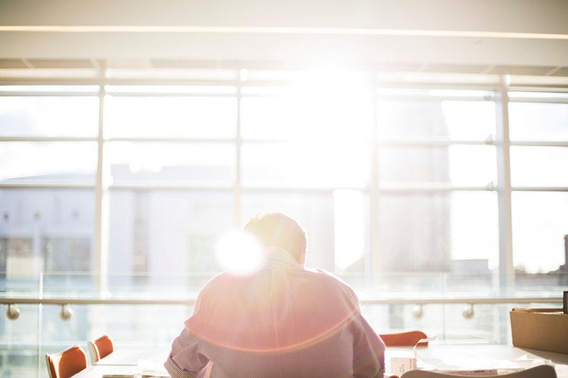 Mann sitzt vor einem sonnigen Fenster und arbeitet.