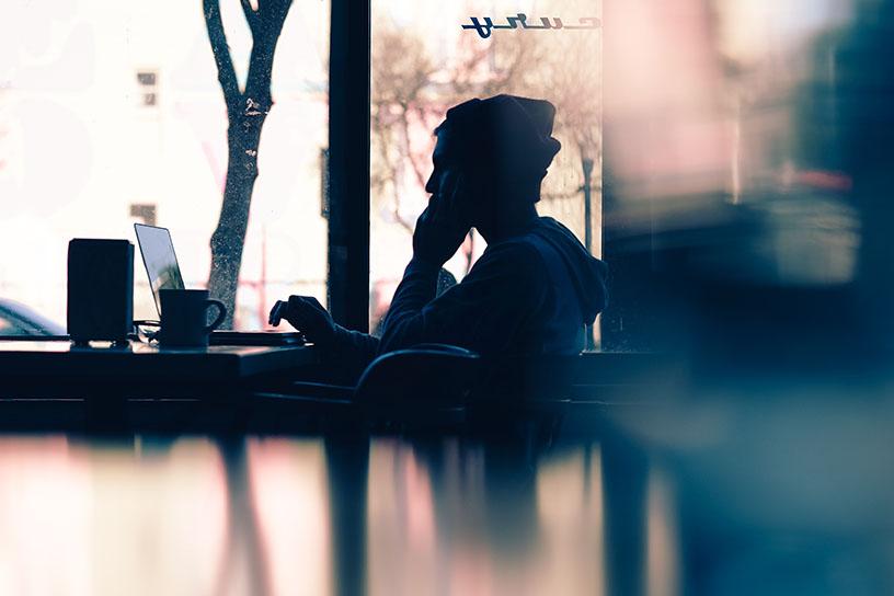 Mensch sitzt vor einem Laptop. Man sieht nur seine Silouette. Man erkennt er sitzt im Profil zum Betrachter.