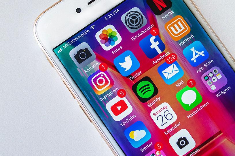 Ein weißes Iphone mit diversen Social Media Apps.