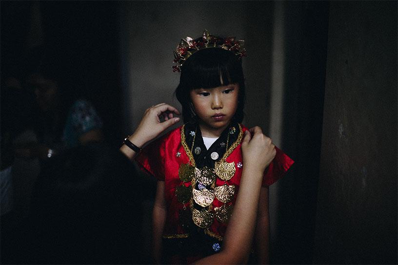 Ein asiatisches Mädchen wird ein traditionelles rotes Kleid angezeogen von Händen aus dem Off. Das Mädchen schaut etwas traurig nach rechts weg.