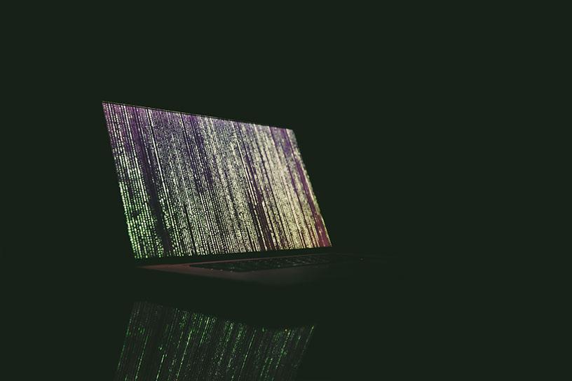Ein Laptop in einem komplett schwarzen Raum. Über den Bildschirm laufen grün, gelbe Zeichenreihen von oben nach unten.