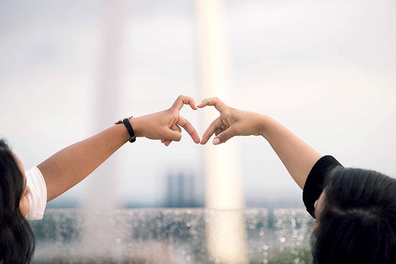 Zwei Menschen formen ein Herz mit ihren Händen. Der Hintergrund ist verschwommen und man erkennt einen Regenbogen sowie Glasscheiben mit Regentropfen.