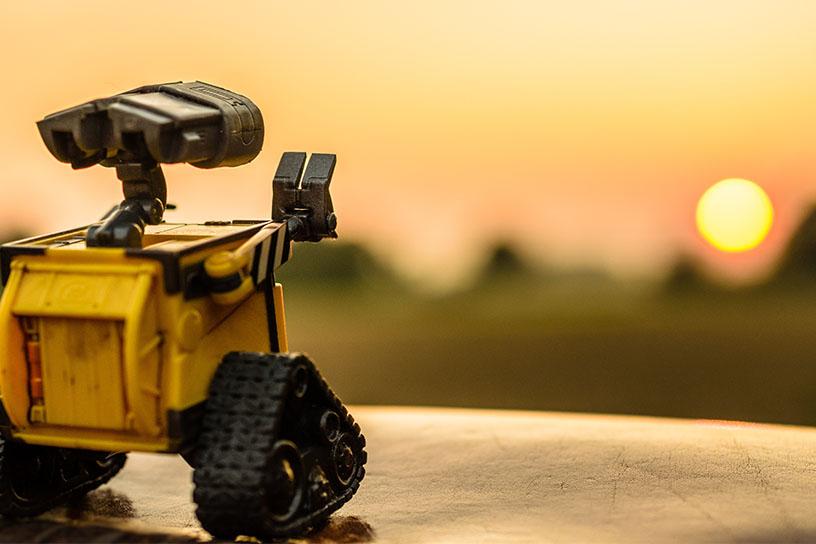 Der Roboter Wall-E schaut in die Fehrne zu einem Sonnenuntergang.