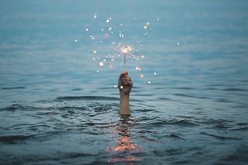 Mensch hält eine Wunderkerze über Wasser, welche brennt. Der Mensch ist komplett unter Wasser und nicht sichtbar, lediglich der Arm.