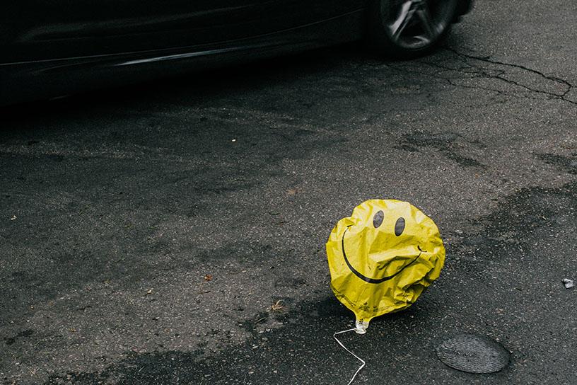 Ein Balloon mit einem Smiley gesicht drauf liegt auf dem Boden. Die Luft ist beihnahe komplett raus. Im Hintergrund sieht man ein Auto vorbei fahren.