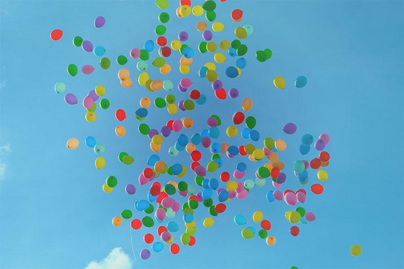 Viele bunte Balloons vor einem blauem Himmel.