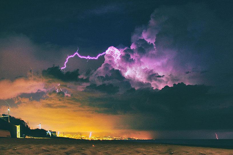 Gewitterwolke mit Blitzen über einem Strand. Im Hintergrund sieht man eine beleuchtete Stadt.