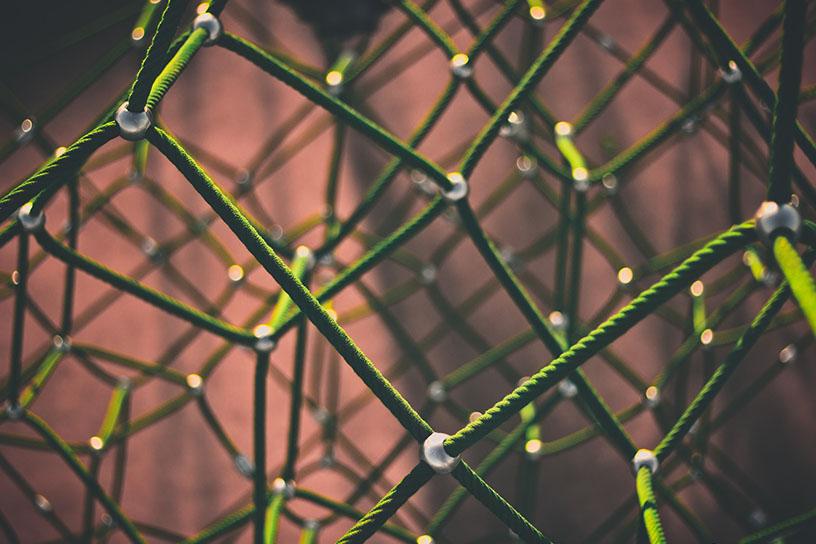 Bild von grünen Fäden, die an metall Perlen zusammen laufen.