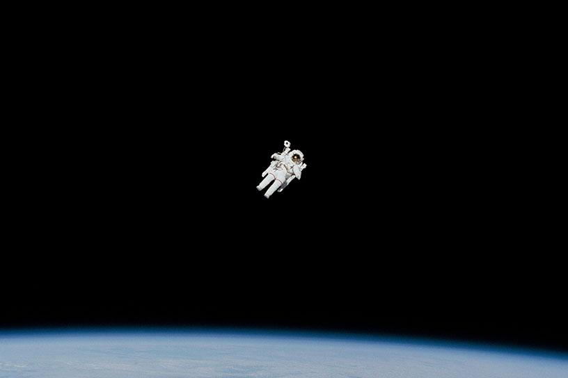 Astronaut im Weltraum. Schwarze Leere, unter ihm eine Erdwölbung.