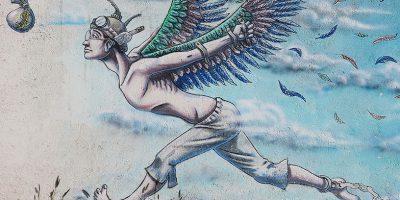 Grafitty von einem Menschen mit selbst angeklebten Engelsflügeln, der einem Sack Geld nachrennt, welcher an einer Angel über seinem Kopf befestigt ist. An seinem Fuß sieht man eine Fessel.
