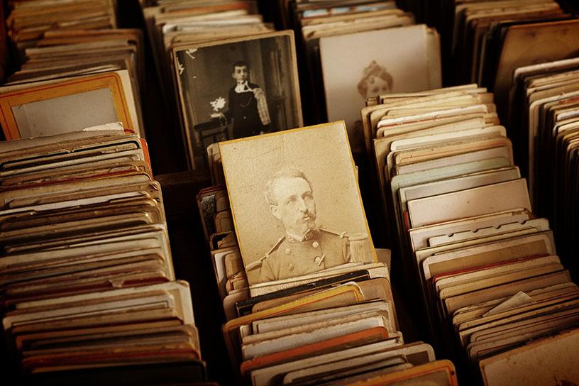 Eine Ansammlung von historischen Photos in einem Aufbewahrungsschrank. Alles ist in Sepia gehalten.