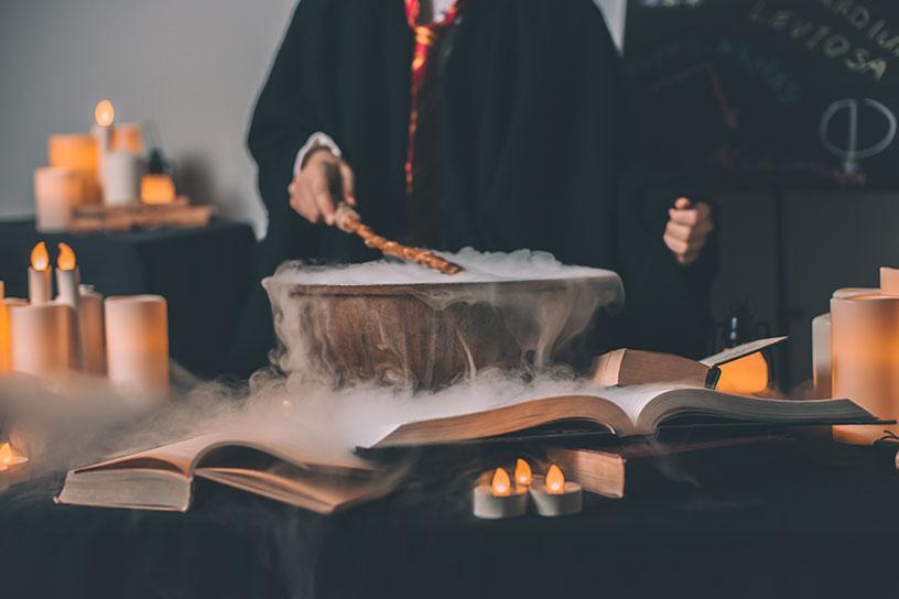 Ein Harry Potter Kittel, mit Zauberstab über eine dampfenden Schüssel, umgeben von Kerzen.
