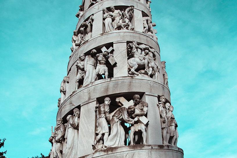 Ein Turm aus Stein. Zwischen den Säulen sind Menschen, die den Turm mit stützen.
