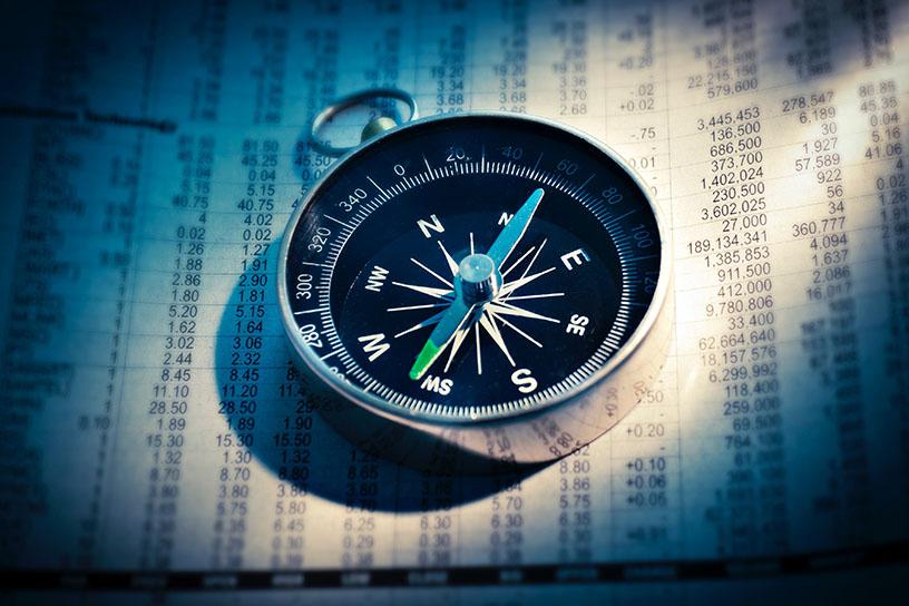 Ein Kompas auf einem Blatt Papier, welches Börsen Kurse dokumentiert.