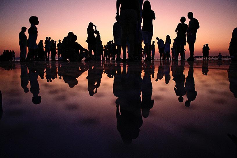 Eine Gruppe Menschen, die als Silouetten vor einem Sonnenuntergang dargestellt sind.