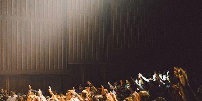 Menschen in einem Saal die ihre Hand erheben.