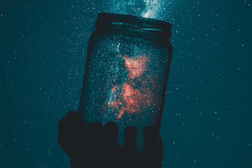 Menschliche Hand die ein Glas hochhält. Im Glas scheint eine Galaxie gefangen zu sein.